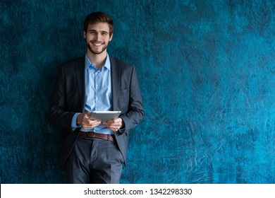 Cool businessman using touchpad on blue background