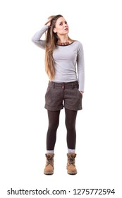 Cool candid spontaneous relaxed unposed hipster woman with hand in hair. Full body isolated on white background.
