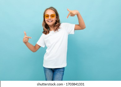 Cool caucasian teenager girl in white t-shirt, yellow glasses smiles and shows herself isolated on blue background