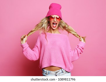 Cool cheerful girl with bright red lips wears modern knitted cap and pink jumper. Hipster style. Youth fashion. Pink Background.