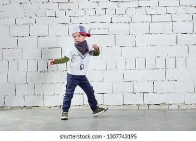 Cool child boy hip hop actively dancing to the music. Cute fashionable kid. Little rapper man wears a cap, sneakers, pants, t-shirt, street style clothes. studio, brick wall background.