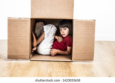 cool child hunched in a tiny cardboard box hiding for protection and confidence from building a small house