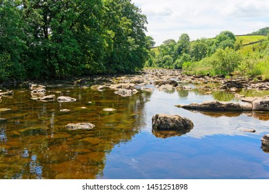 The cool, clear water of the rock strewn River Ribble near the village of Stainforth.