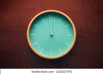 Cool clock on grunge wall showing minute to noon or midnight