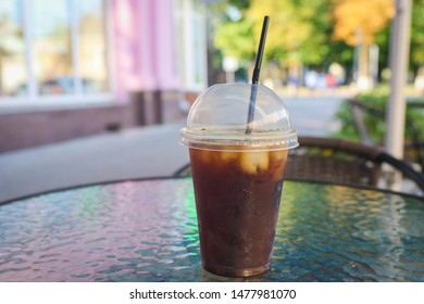 A cool coffee and ice drink on a glass table in summer