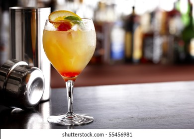Cool, colorful summer drink with orange, lime and cherry, shot in bar with shaker