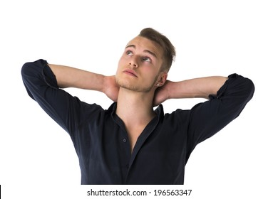 Cool confident blond young man with blue shirt, hands behind head, isolated on white