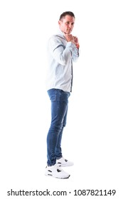 Cool confident masculine guy getting dressed holding light blue shirt collar looks at camera. Full body isolated on white background.