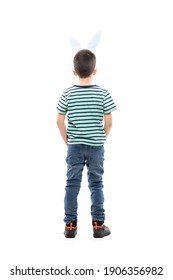 Cool confident young boy with Easter bunny ears and hands in pockets looking away watching copy space. Full length isolated on white background.