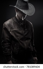 Cool cowboy in jacket with cigarette over dark background