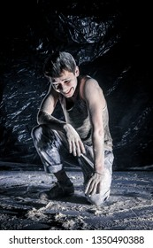 cool dirty сhinese  guy dancer in style of bboying doing complex tricks on floor in Studio filled with flour on black background. concept of space dance on surface of planet moon