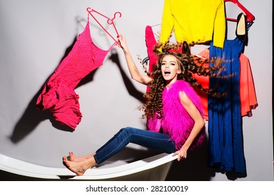 Cool emotional young woman with curly hair in pink fur vest and blue jeans sitting in white bathtub amid colorful clothes pink orange red blue colors on grey wall background, horizontal picture