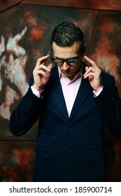 Cool fashion man in glasses standing over industrial background