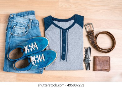 cool fashion men's casual outfit on wooden table, trendy in summer, t-shirt, blue jeans pants, sneaker, watch, wallet and belt, top view