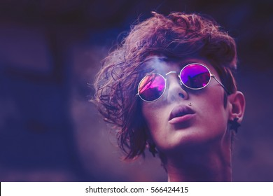 Cool fashion model with modern pop hair styling wearing round color sunglasses smokes cigarette.Stylish portrait of smoking young woman in hipster look