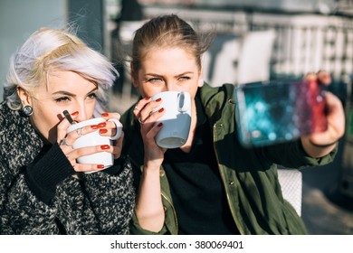 Cool fashionable girls taking a selfie in coffee shop