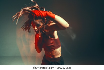 Cool female fighter in boxing bandages trains in studio in red neon light. Mixed martial arts poster. Long exposure shot
