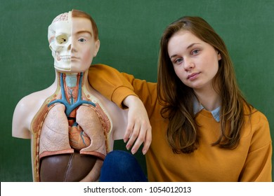 Cool female high school student portrait with an artificial human body model. Student having fun in Biology class. Education concept.