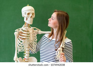 Cool female high school student portrait with an artificial human body skeleton. Student having fun in Biology class. Education concept.
