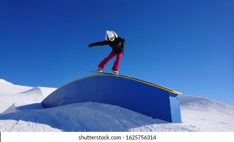 Cool female snowboarder does a jib trick along a railing in a big snow park in Banff, Canada. Athletic woman on active winter vacation, slides along a rail set up in a fun park in a big ski resort.