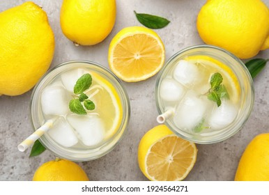 Cool freshly made lemonade and fruits on grey table, flat lay