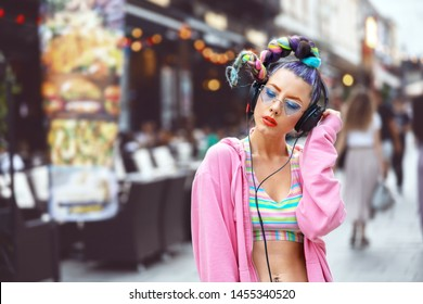Cool funky young woman with trendy eyeglasses listening music on headphones outdoor - hipster girl with sunglasses and piercings enjoy music vibes – street fashion look with girl teen with crazy hair