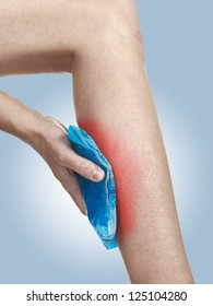 Cool gel pack on a swollen hurting calf. Medical concept photo. Isolation on a white background. Color Enhanced skin with read spot indicating location of the pain.