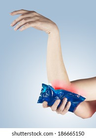 Cool gel pack on a swollen hurting Elbow. Medical concept photo.