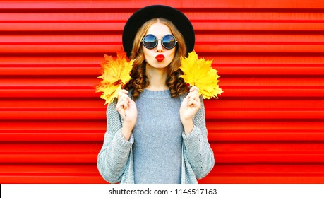 Cool girl autumn portrait woman with yellow maple leaves on a red background