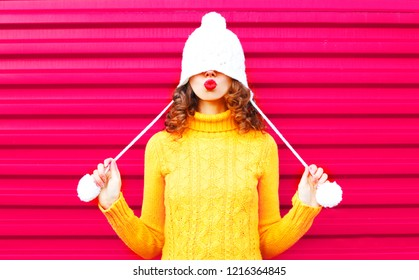 Cool girl blowing red lips makes air kiss wearing colorful knitted hat, yellow sweater over pink background
