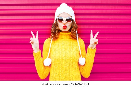 Cool girl blowing red lips wearing a colorful knitted yellow sweater hat over pink background