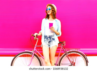 Cool girl with coffee or juice cup and retro vintage bicycle over colorful pink background