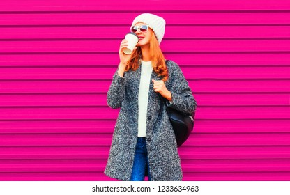 cool girl drinking tasty coffee wearing gray coat, knitted hat on colorful pink wall background