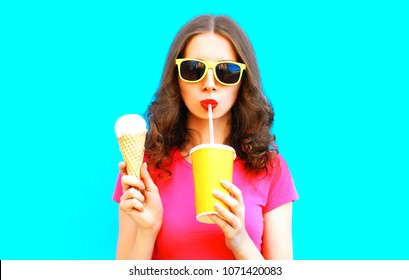 Cool girl drinks fruit juice from cup and holds ice cream over colorful blue background