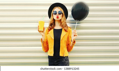 Cool girl  having fun blowing red lips sends air kiss holding black air balloon, cup of fruit juice in round hat