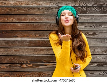 Cool girl having fun listens music in headphones over wooden background. Autumn time.
