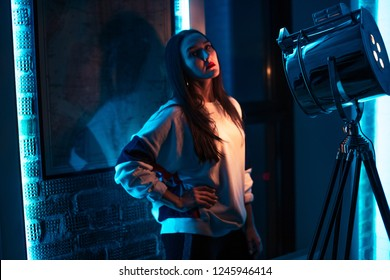 cool girl with long black straight hair in the studio. close up side view photo. model displaying a stylish sportswear. casual wear. photo session with searchlight