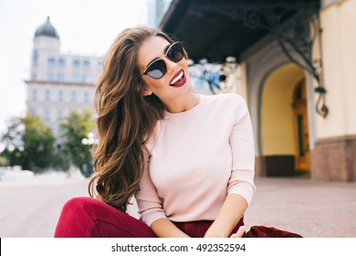 Cool girl with long hairstyle and vinous lips having fun in the city. She wears sunglasses and smiling to camera with snow-white smile.