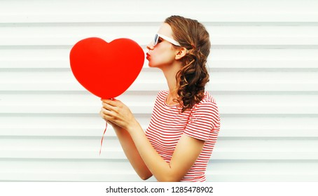 Cool girl making air kiss with red balloons heart shape over white background