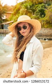 Cool girl on beach in sunhat and shades