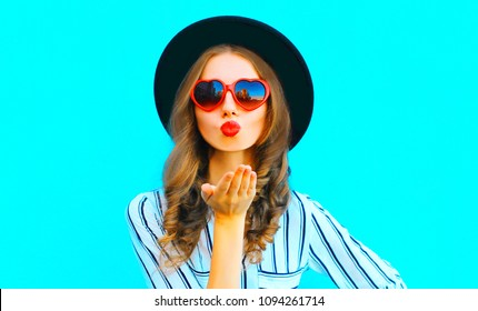 Cool girl with red lips is sends an air kiss in a sunglasses shape of heart over  blue background