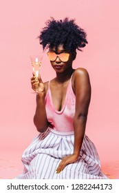 Cool girl with sunglasses holding champagne glass, isolated on pink