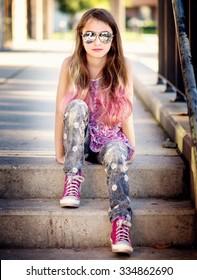 Coole Frau mit Sonnenbrille und rosafarbenem Haar auf Stufen
