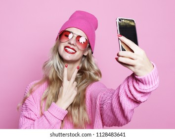 cool girl taking photo makes self portrait on smartphone wearing pinkl clothes over pink background