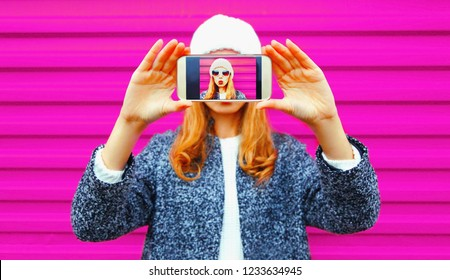 Cool girl taking selfie her face close-up by smartphone, hipster having fun blowing lips sends air kiss on colorful wall background