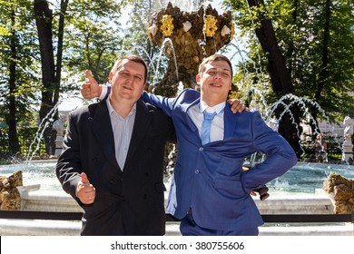 Cool groom and his father near fountain in summer park