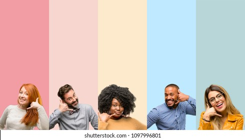 Cool group of people, woman and man happy and excited making showing call me gesture with hand shaped like telephone