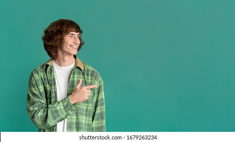 Cool guy with curly hair pointing aside on color background, space for design