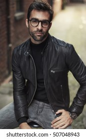 Cool guy posing in glasses and leather jacket