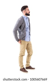 Cool handsome bearded fashion model in casual wear posing. Side view. Full body length portrait isolated on white background.